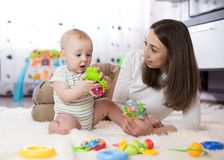 滑稽的使用在托儿所的婴孩和少妇 获得愉快的家庭与五颜六色的玩具的乐趣在家 免版税库存照片