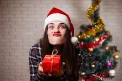 滑稽的做鬼脸的逗人喜爱的快乐的妇女画象圣诞老人盖帽的与 免版税图库摄影