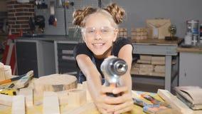 滑稽的十岁的女孩画象在拿着一个电子钻子的木木匠业方面,摆在照相机 建造者一点 股票录像