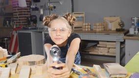 滑稽的十岁的女孩画象在拿着一个电子钻子的木木匠业方面,摆在照相机 建造者一点 影视素材