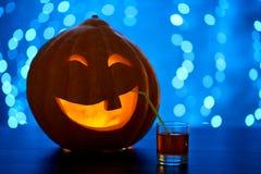 滑稽的南瓜为万圣夜微笑的和饮用的鸡尾酒做准备 库存照片