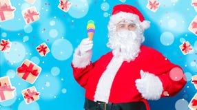 滑稽的圣诞老人获得一个乐趣用冰淇凌 库存照片