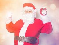 滑稽的圣诞老人获得与闹钟的一个乐趣 图库摄影