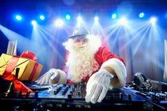滑稽的圣诞老人DJ在光柱混合音乐 免版税库存图片