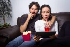 滑稽的夫妇观看电影 他们如此坐沙发在h 免版税库存图片