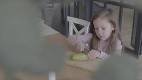 滑稽的女孩坐椅子在桌上,切口夏南瓜,帮助她的母亲烹调食物 适当的育儿 股票视频