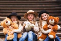 滑稽的女孩女朋友坐有软的玩具的台阶在公园 免版税库存图片