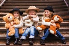 滑稽的女孩女朋友坐有软的玩具的台阶在公园 免版税库存照片