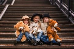 滑稽的女孩女朋友坐有软的玩具的台阶在公园 库存照片