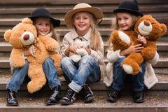 滑稽的女孩女朋友坐有软的玩具的台阶在公园 库存图片