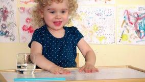 滑稽的女孩孩子倾倒在桌之上的水并且洒它与棕榈 激动的湿孩子 股票录像