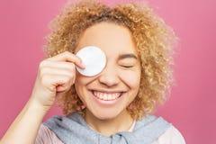 滑稽的女孩拿着在她眼睛和微笑的一块小白色海绵 并且她闭上了她的其他眼睛 15个妇女年轻人 免版税库存图片