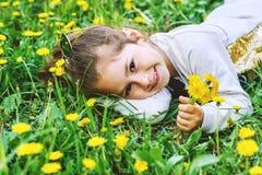 滑稽的女孩用说谎在草的蒲公英 免版税库存照片