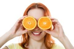 滑稽的女孩纵向,拿着在眼睛的桔子 免版税图库摄影
