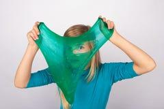 滑稽的女孩holdin在她的面孔前面的透明软泥和看通过它的孔 库存图片