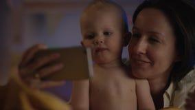 滑稽的婴孩坐在与他的母亲的坏的和她显示他与她的电话关闭的动画片 股票录像