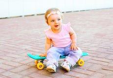 滑稽的婴孩坐滑板 免版税库存图片