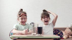 滑稽的孩子做一次化工试验并且混合试剂 孩子是惊奇和愉快的观看化学制品