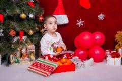 滑稽的孩子发现了蜜桔在圣诞树下 库存图片
