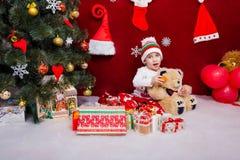 滑稽的孩子喂养蜜桔玩具熊 库存照片