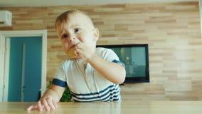 滑稽的孩子在饼干的桌上上升 有孩子概念的好奇录影 影视素材