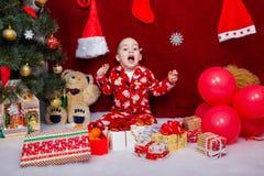 滑稽的孩子对圣诞节礼物的数量高兴 免版税库存图片