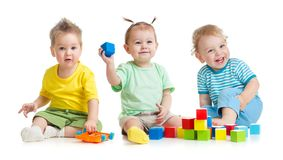 滑稽的孩子编组演奏在白色隔绝的五颜六色的玩具 图库摄影
