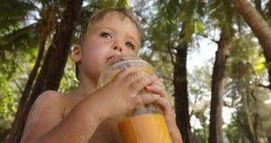滑稽的孩子饮用的果子新鲜在热带 股票视频