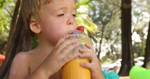 滑稽的孩子饮用的果子新鲜在热带 股票录像