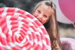 滑稽的小女孩吃大棒棒糖在她的党 免版税库存照片