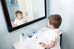 滑稽的小孩在卫生间镜子做看他自己的面孔 免版税库存照片