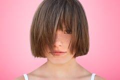 滑稽的小孩子用头发盖面孔,展示她新的发型,感觉象真正的模型,摆在反对桃红色演播室背景 H 图库摄影