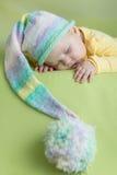 滑稽的帽子的休眠的婴孩在绿色 免版税库存照片