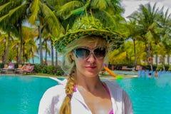 滑稽的帽子的年轻可爱的白种人妇女在热带海滩 库存照片