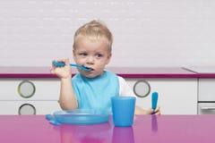 滑稽的年轻男婴画象蓝色围嘴有叉子的和刀子的在他的在高脚椅子的手上在现代厨房里 免版税图库摄影