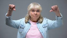 滑稽的年长女性显示的拇指下来打手势,怏怏不乐对于州政府 影视素材
