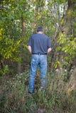 滑稽的幽默人小便在森林 免版税图库摄影