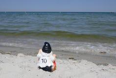 滑稽的庭院地精,与第10的足球迷在他的球衣背面 他坐在海滩做假日在se 库存照片