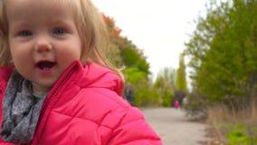 滑稽的微笑的女婴在公园 股票录像