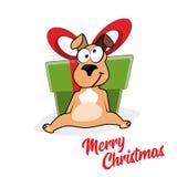滑稽的微笑的狗动画片画象在圣诞老人帽子的有大礼物盒的 免版税库存照片