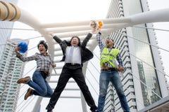 滑稽的快乐的跳跃在空气和举有工作的商人和工程师胳膊对成功 免版税库存照片