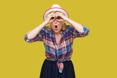 滑稽的惊奇的现代时髦的成熟妇女画象便装样式的与与双筒望远镜的帽子身分打手势和看与 库存照片
