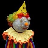 滑稽的手工制造玩偶小丑被做一个老足球 隔离 库存照片
