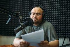 滑稽的无线电赠送者或主人在电台演播室,工人画象  库存照片