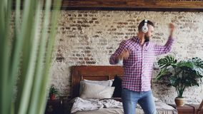 滑稽的有胡子的人获得乐趣,跳舞并且跳与吉他,当听到与无线耳机时的音乐 影视素材