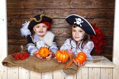 滑稽的男孩和女孩海盗服装的在演播室有风景的为万圣夜 免版税库存图片