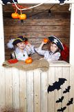 滑稽的男孩和女孩海盗服装的在演播室有风景的为万圣夜 免版税库存照片