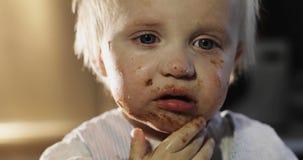 滑稽的男孩抹上他的在巧克力的面孔 股票视频