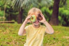 滑稽的男孩用多福饼 孩子获得乐趣用多福饼 孩子的鲜美食物 愉快的时间室外用甜食物 库存图片