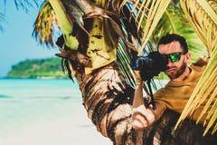 滑稽的男性无固定职业的摄影师摄影师在一个热带海滩的一棵树后掩藏为一台暗藏的照相机照相 免版税图库摄影